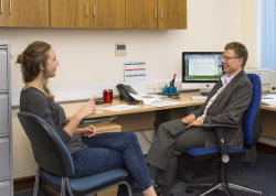 A female graduate student talks with Support Services Manager Marita Walsh