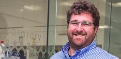 Head and shoulders of Professor Oren Scherman wearing blue shirt looking at camera